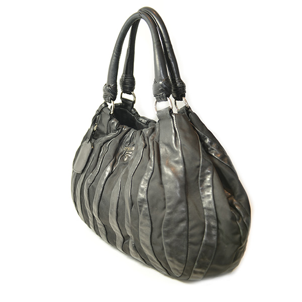 Side view of on sale pre-owned Prada Nylon Leather Quilted Shoulder Bag in black with slouch design and double leather handles.