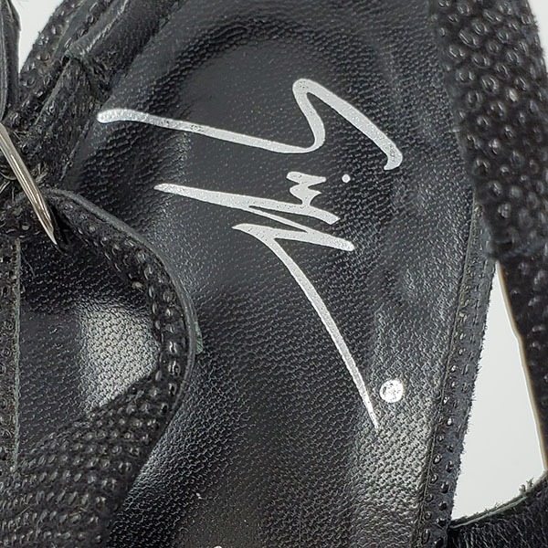 Close up brand logo of on sale pre-owned black Guiseppe Zanotti Glitter Peep-toe Heels, with adjustable strap.
