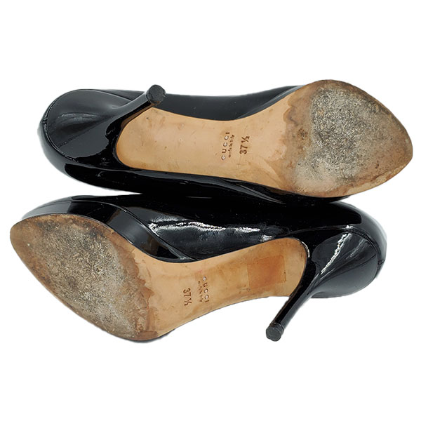 Soles of on sale pre-owned black Gucci Vintage Patent Leather Pumps, with front platform and skinny heels.