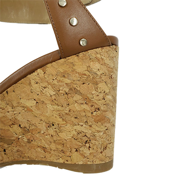 Back close up of on sale pre-owned Jimmy Choo Leather Wedge Sandals in tan leather, with gold-tone studs.