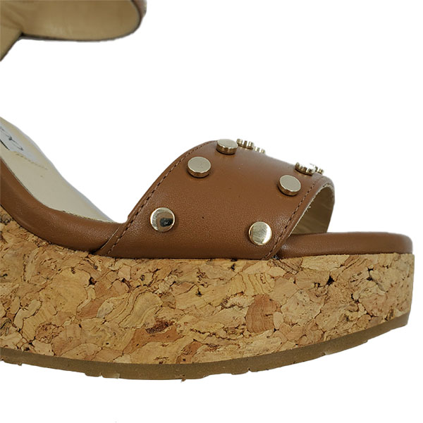 Front close up of on sale pre-owned Jimmy Choo Leather Wedge Sandals in tan leather, with gold-tone studs.