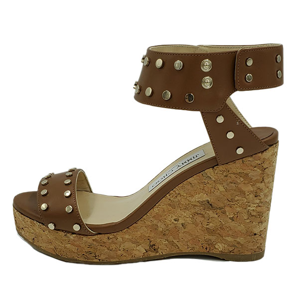 On sale pre-owned Jimmy Choo Leather Wedge Sandals in tan leather, with gold-tone studs.