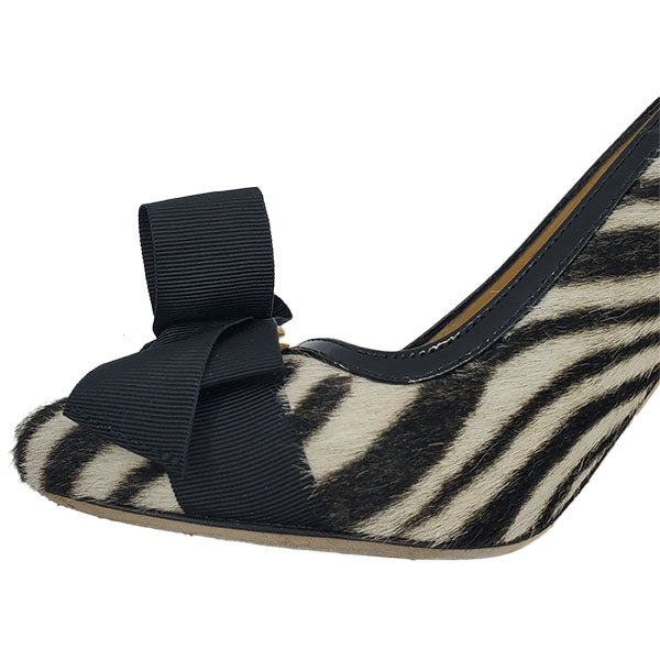 Close up front view of on sale pre-owned Kate Spade Animal Print Pumps with Bow, with black and white zebra print.