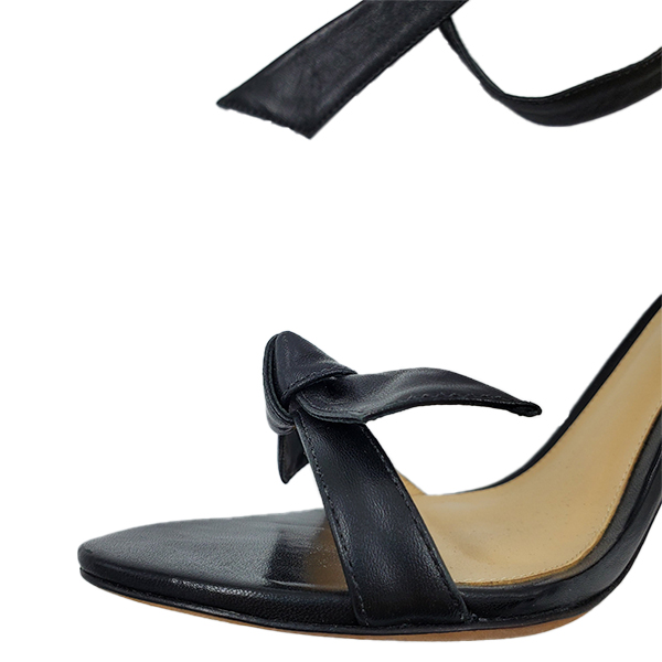 Close up front view of pre-owned Alexandre Birman Leather Strappy Heels in black, with front leather bow.