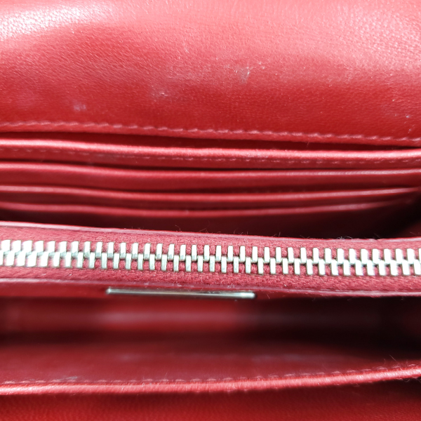 Compartments of pre-owned Prada Vintage Patent Leather Crossbody Bag, with soft red interior.