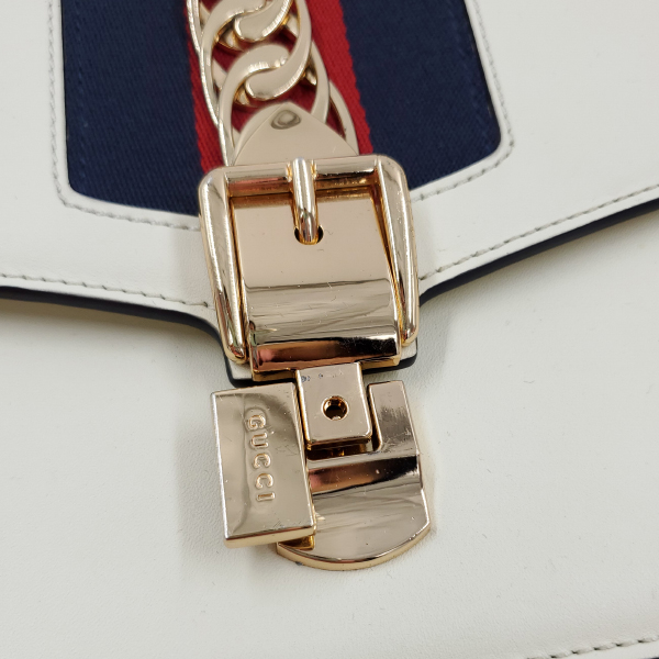 Close up of pre-owned Gucci Sylvie Small Shoulder Bag in white, with button closure.
