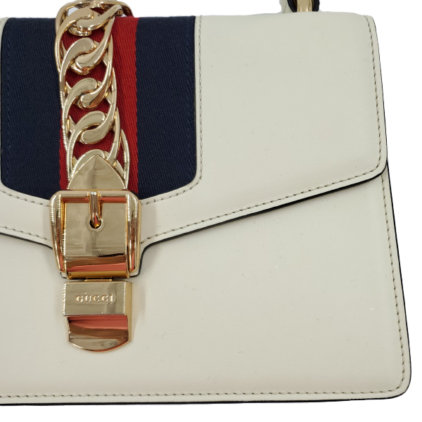 Close up of pre-owned Gucci Sylvie Small Shoulder Bag in white, with metal chain and button closure.